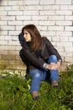 Schöne junge Frau, die in einer Backsteinmauer sitzt stockfotos