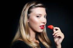 Schöne junge Frau, die Erdbeere hält Stockfotografie