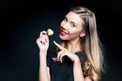 Schöne junge Frau, die Erdbeere hält Stockfoto