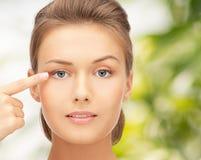 Schöne junge Frau, die Finger auf ihr Auge zeigt lizenzfreie stockbilder