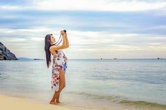 Schöne junge Frau, die Foto mit der Kamera mirrorless auf macht Stockbild