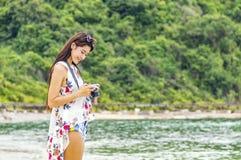 Schöne junge Frau, die Foto mit der Kamera mirrorless auf macht Stockfotografie