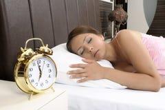 Schöne junge Frau, die friedlich auf Bett schläft lizenzfreies stockfoto