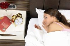 Schöne junge Frau, die friedlich auf Bett schläft stockfoto