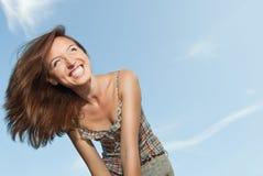 Schöne junge Frau, die gegen den Himmel lächelt lizenzfreie stockfotografie