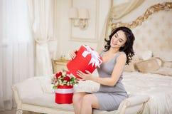 Schöne junge Frau, die Geschenkbox hält Stockfotografie