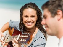 Schöne junge Frau, die Gitarre auf Strand spielt Lizenzfreies Stockbild