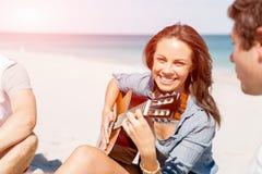 Schöne junge Frau, die Gitarre auf Strand spielt Stockbild