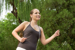 Schöne junge Frau, die in grünen Park am Sommertag läuft lizenzfreie stockfotografie