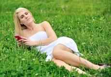 Schöne junge Frau, die in Gras - Musik legt Stockbild
