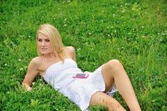 Schöne junge Frau, die in Gras - Musik legt Stockfotografie