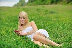 Schöne junge Frau, die in Gras - Musik legt Stockfotos