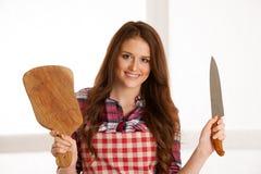 Schöne junge Frau, die hölzernes bord und Messer in der Küche hält Stockfoto