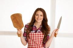 Schöne junge Frau, die hölzernes bord und Messer in der Küche hält Lizenzfreie Stockfotografie