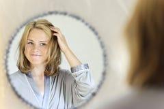 Schöne junge Frau, die Haar tut Stockfoto