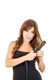 Schöne junge Frau, die Haarstrecker verwendet Stockfotografie