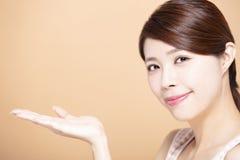 Schöne junge Frau, die an Hand Schönheitsprodukt leeren Raum zeigt lizenzfreies stockbild