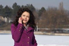 Schöne junge Frau, die am Handy spricht Lizenzfreies Stockfoto