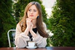 Schöne junge Frau, die heißen Kaffee im Sommergarten trinkt stockfoto