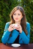 Schöne junge Frau, die heißen Kaffee im Sommergarten trinkt lizenzfreie stockfotografie