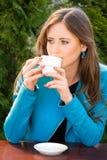 Schöne junge Frau, die heißen Kaffee im Sommergarten trinkt stockfotos