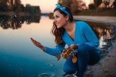 Schöne junge Frau, die am Herbstflussbankspritzwasser sitzt und Niederlassungen hält stockfotografie