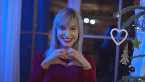 Schöne junge Frau, die Herzsymbol und -c$lächeln zeigt Lizenzfreies Stockfoto