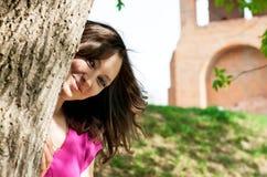 Schöne junge Frau, die hinter einem Baum sich versteckt Stockbild