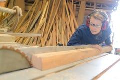 Schöne junge Frau, die Holz in der Werkstatt kontrolliert Lizenzfreie Stockbilder