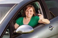 Schöne junge Frau, die ihr Autoschlüssel zeigt Lizenzfreie Stockfotografie