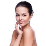 Schöne junge Frau, die ihr Gesicht berührt lizenzfreie stockfotos