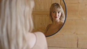 Schöne junge Frau, die ihr Gesicht in einem Spiegel überprüft Lizenzfreie Stockfotos