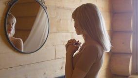 Schöne junge Frau, die ihr Gesicht in einem Spiegel überprüft Stockbilder
