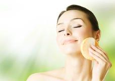 Schöne junge Frau, die ihr Gesicht wäscht Lizenzfreie Stockfotografie