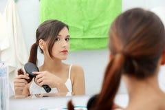 Schöne junge Frau, die ihr Haar aufträgt lizenzfreie stockbilder