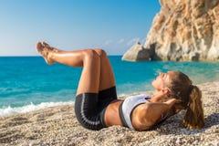 Schöne junge Frau, die ihre ABS auf dem Strand ausarbeitet lizenzfreies stockbild