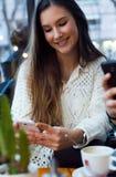 Schöne junge Frau, die ihren Handy am Caféshop verwendet Stockbild