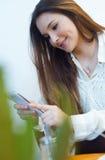 Schöne junge Frau, die ihren Handy am Caféshop verwendet Stockbilder