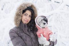 Schöne junge Frau, die ihren kleinen weißen Hund im Winterwald umarmt schneiende Zeit Lizenzfreies Stockfoto
