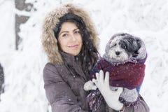 Schöne junge Frau, die ihren kleinen weißen Hund im Winterwald umarmt schneiende Zeit Lizenzfreies Stockbild