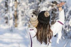 Schöne junge Frau, die ihren kleinen weißen Hund im Winterwald umarmt schneiende Zeit Stockfotos