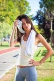 Schöne junge Frau, die ihren Schweiß mit einem Tuch säubert stockfotos