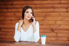 Schöne junge Frau, die ihren Smartphone verwendet und Kaffee trinkt stockfoto