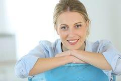 Schöne junge Frau, die im Büro sitzt Lizenzfreies Stockfoto