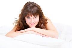 Schöne junge Frau, die im Bett sich entspannt Lizenzfreie Stockfotografie