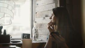 Schöne junge Frau, die im Café sitzt, den Smartphone hält und das Fenster, allein träumend betrachtet stock video