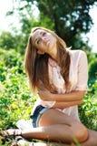 Schöne junge Frau, die im Garten sich entspannt Lizenzfreie Stockfotos