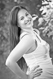 Schöne junge Frau, die im grünen Park auf Sonne aufwirft lizenzfreie stockfotografie