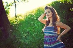 Schöne junge Frau, die im grünen Park aufwirft stockfotos