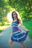 Schöne junge Frau, die im grünen Park aufwirft lizenzfreie stockfotografie